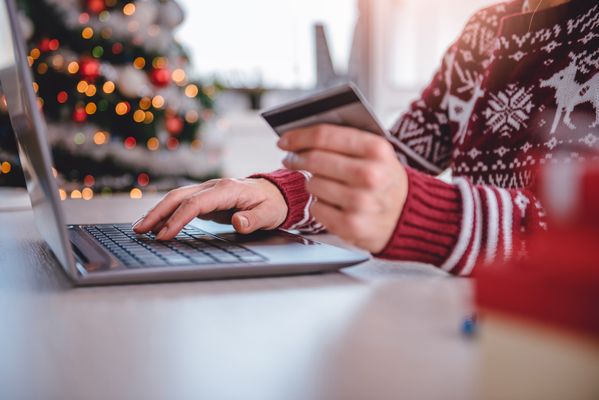 woman buying something on her laptop computer in front of a christmas tree